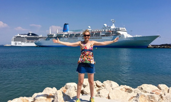 Sarah doing a i have conquored pose on the dock with the ship in the background