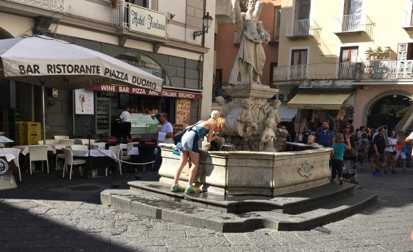 Sarah drinking from the natural water fountain in the Amalfi square