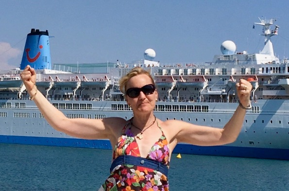 Sarah raising her arms in victory stood in front of the Thomson Spirit ship