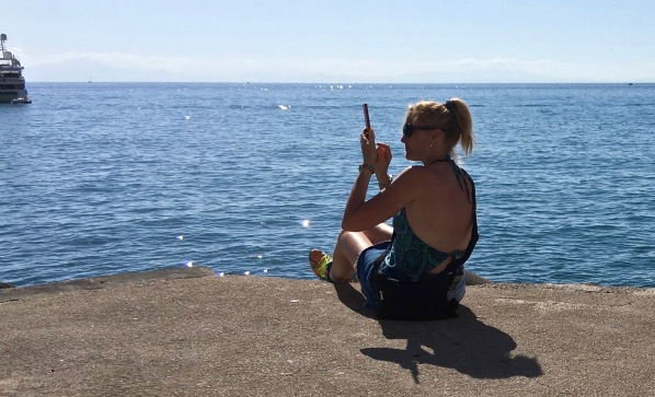 Sarah sat on the very small dock with her feet off the end taking a photo of a ship that is fust in shot