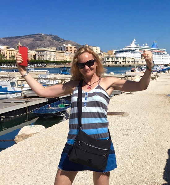 Sarah showing her guns in a victory pose stood in front of lots of colourful boats in the dock at Sicily