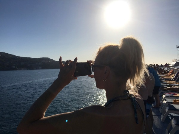 Sarah taking a photo of the sunset and landscape from the ship