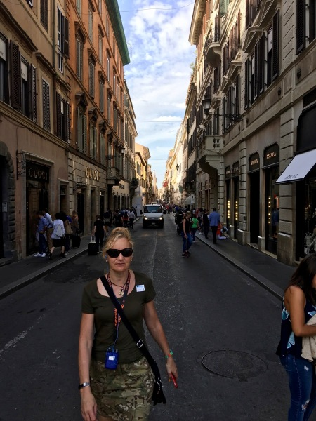 Sarah walking towards the camera down the centre of a busy street in Rome with tall building s on either side