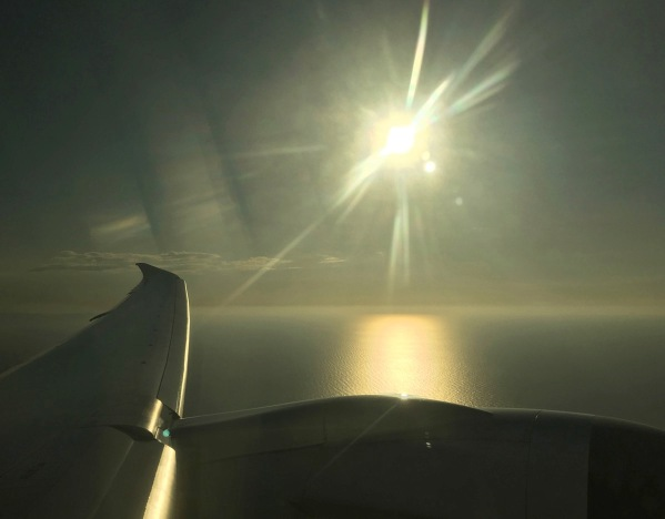 view from the plane window in med flight with the wind on the lower left and the sun spiking down from the top and creating glorious light