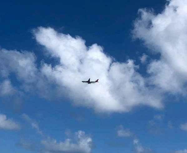 photo of a airplane flying through a fluffy white cloud in the blue sky