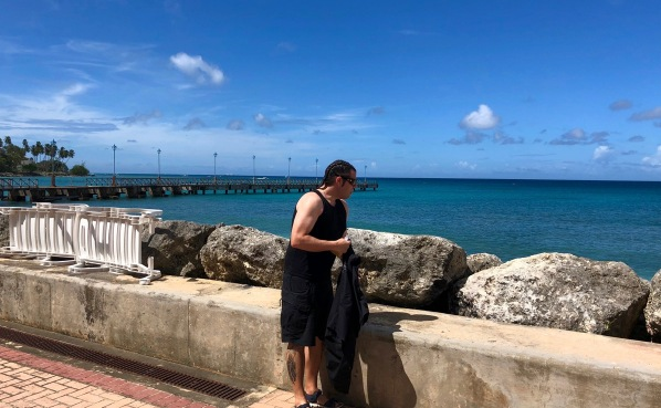 me stood unwrapping the coconut slice in front of the sea and a wall