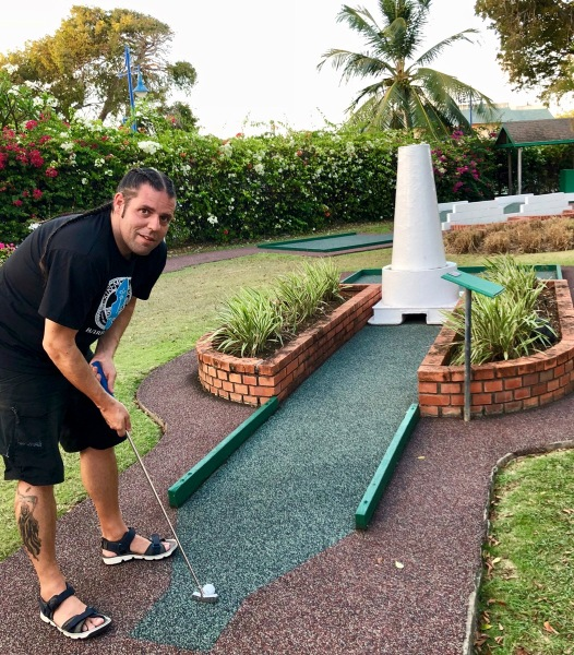 Me looking towards the camera whilst taking a shot on the lighthouse crazy golf course at southern palm Barbados