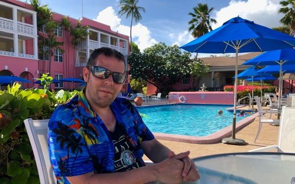 Me sat in blue Caribbean shirt next to the swimming pool and the beach