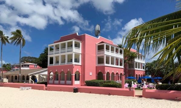 Photo of the pink hotel taken from the beach with palm trees around